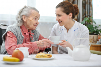caregiver and senior woman smiling while holding a cup