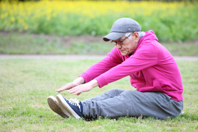 Senior Asian man wearing pink parka with gray cap doing exercise outdoor